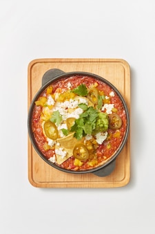 밝은 회색 배경, 복사 공간에 나무 보드에 냄비에 토마토, 피망, 야채와 허브와 함께 튀긴 계란에서 중동 전통 요리 shakshuka. 평면도.