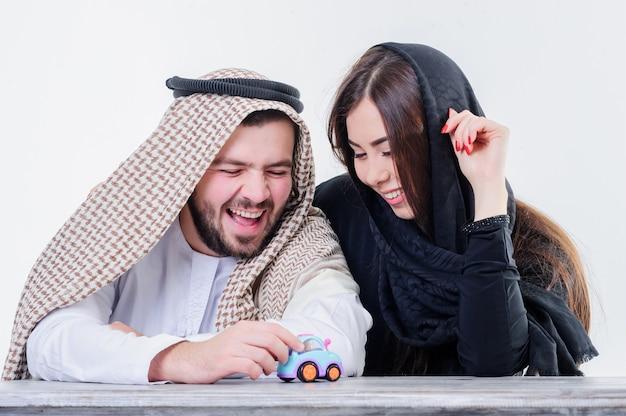 Средневосточный стиль одетый суп ян играет с игрушечной машинкой.