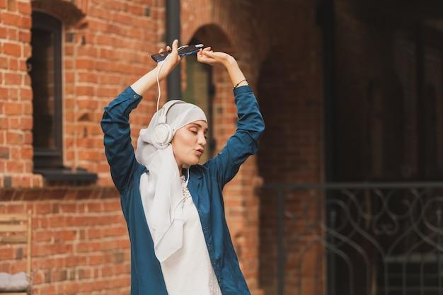 헤드폰으로 음악을 듣고 야외에서 춤을 추는 히잡을 쓴 중동 여성. 여성 독립과 페미니즘 개념입니다.