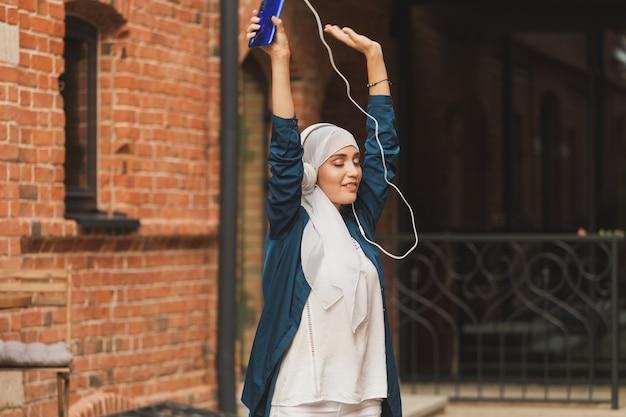 헤드폰으로 음악을 듣고 야외에서 춤추는 히잡을 쓴 중동 여성
