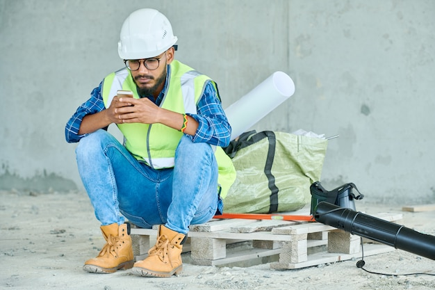 Middle eastern workman using smartphone