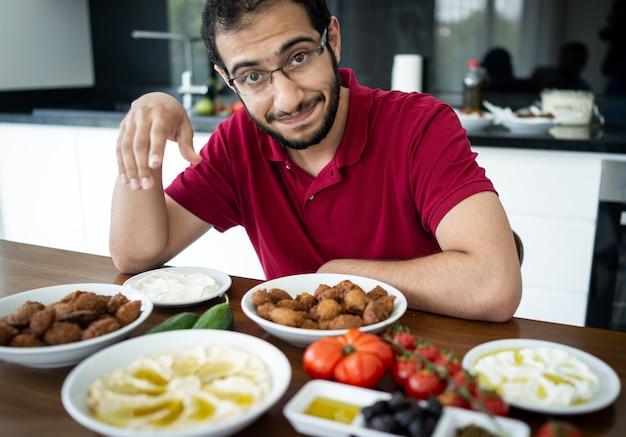 Ближневосточный молодой человек сидит и ест в одиночестве традиционную еду