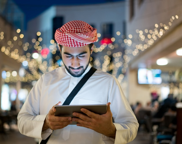 Middle eastern young man with tablet in city at night