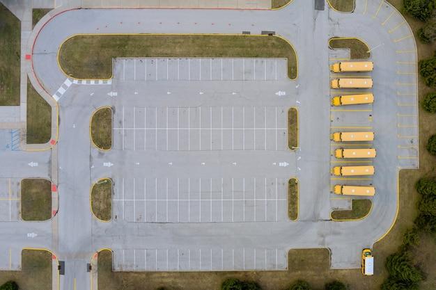 高校の近くに停車している黄色いスクールバスの日中