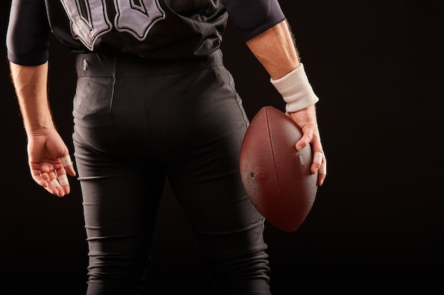 The middle part, of an american football player in black uniform with a ball on a black surface, copy space, back view
