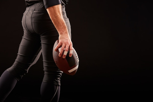 The middle part, of an american football player in black uniform with a ball on a black surface, copy space, side view