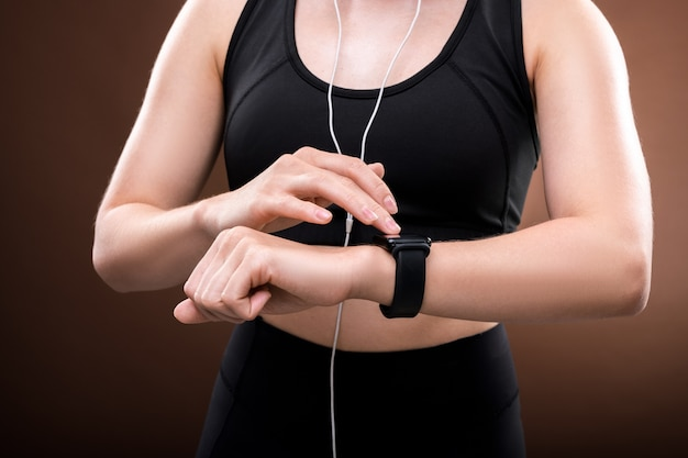 Middle section of young sportswoman in black tracksuit listening to music in earphones and touching her wristwatch in isolation