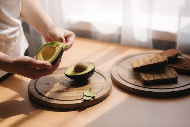 Средний выбор женской таблетки авокадо на деревянной доске дома. концепция вегетарианской пищи.