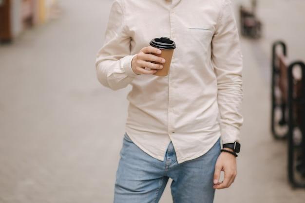 街の真ん中の男性がコーヒーを飲みながら立っています。