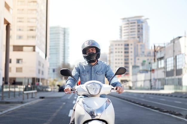 Средний снимок молодого мотоциклиста, остановившегося на светофоре в барселоне, мужчина проезжает через ...
