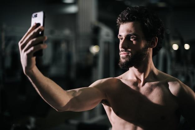 스마트폰으로 셀카 사진을 찍는 자신감 있는 수염 난 젊은이의 중간 샷 초상화