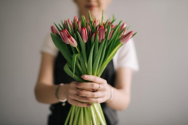 흰색 바탕에 꽃다발을 들고 웃는 여성 꽃집의 중간 샷 초상화