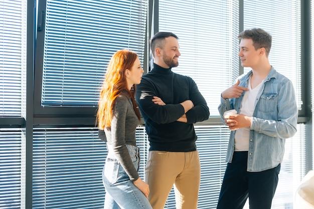 현대 사무실에서 커피를 마시며 즐거운 대화를 나누는 행복한 젊은 사업가 3명의 중간 사진. 자신감 넘치는 동료들은 즐거운 커뮤니케이션을 즐기고 창으로 프로젝트에 대해 토론합니다.