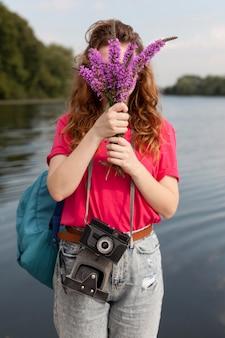 湖の近くでラベンダーを保持しているミドルショットの女性