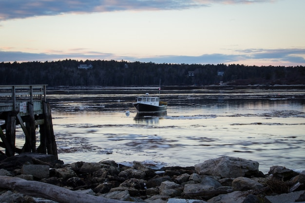 Middle size fishing boat cruising by the shore in the sea close to a rocky beach before dusk