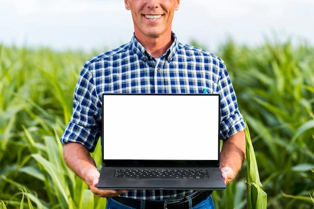 ノートパソコンのモックアップを持って中年男性