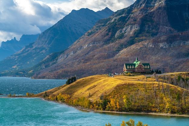 Срединный берег озера уотертон в утре солнечного дня сезона листвы осени. достопримечательности в национальном парке уотертон-лейкс, альберта, канада.