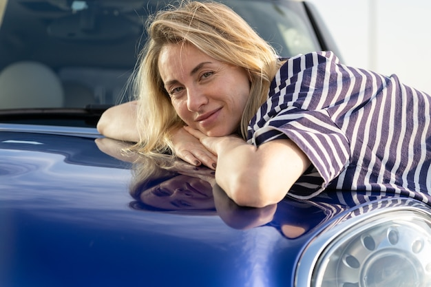 Middle woman driver embracing hood of car after detailing polishing car insurance advertisement