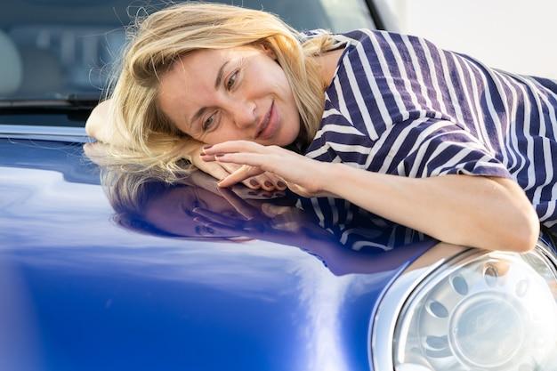 자동차 보험 광고를 자세히 설명한 후 자동차 후드를 껴안은 중간 여성 운전자