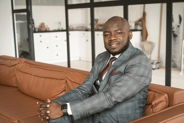 中年の男は、ロフトアパートで笑顔とカメラを見ているアフリカ系アメリカ人のビジネスマンのソファに設定します...