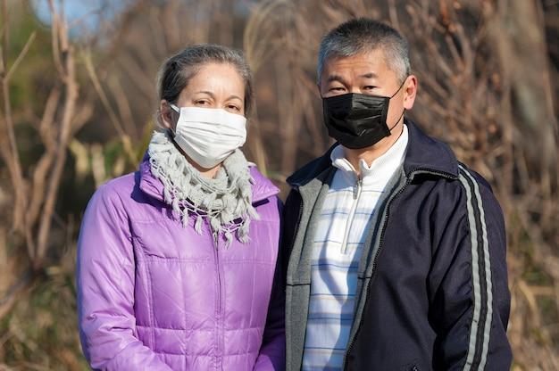 Азиатская пара среднего возраста на открытом воздухе в хирургической маске для защиты от коронавируса