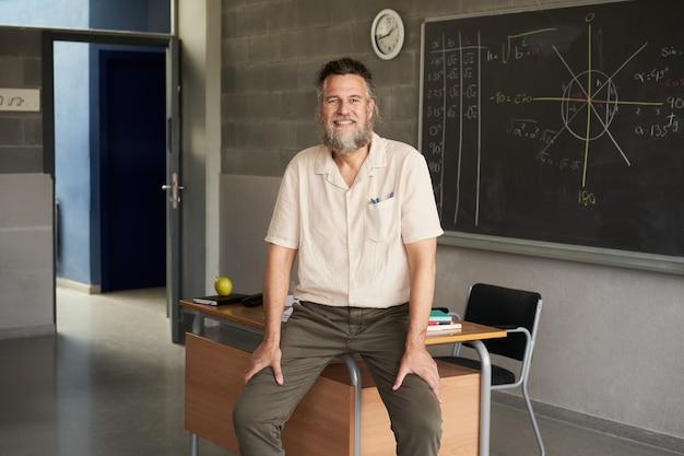 中年のひげを生やした男性教師が教室でカメラを見て幸せで熱心な教師
