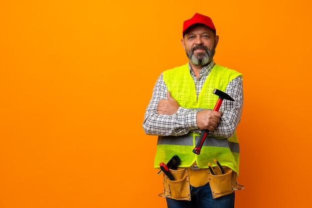 주황색 배경에 도구가 있는 유니폼과 안전모를 입은 중년의 수염 난 남자 빌더