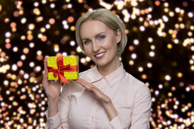 Middleaged beautiful woman is showing a present box