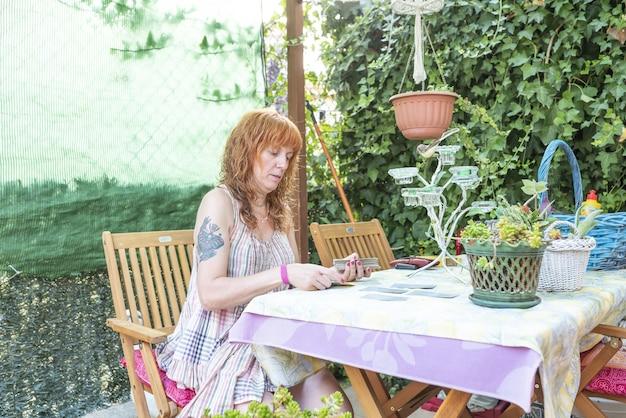 Кавказская женщина среднего возраста бросает карты таро для чтения таро