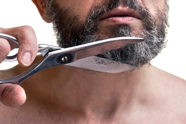 中年男性は大きなはさみを使ってひげを切る