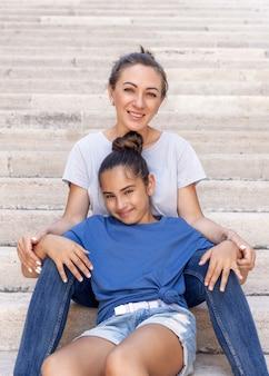 屋外の石の階段に座っている中年の母と彼女の子供の娘