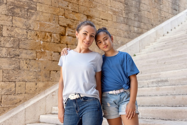 Middleaged mother and her kid daughter standing on stone stairs outdoor tshirts mockup