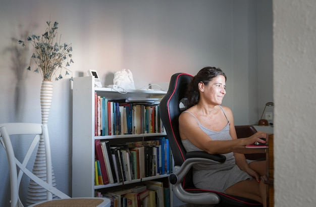 Middleaged spanish brunette woman teleworking in home office with books