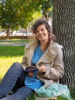 Женщина средних лет с книгой в парке, она сидит на траве с книгой, смотрит в камеру и ...