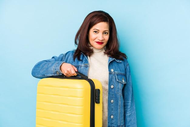 スーツケースを持っている中年のラテン旅行者の女性は、幸せ、笑顔、陽気な孤立しました。
