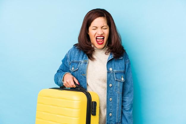 非常に怒って攻撃的な叫び声を孤立させたスーツケースを持っている中年のラテン旅行者の女性。