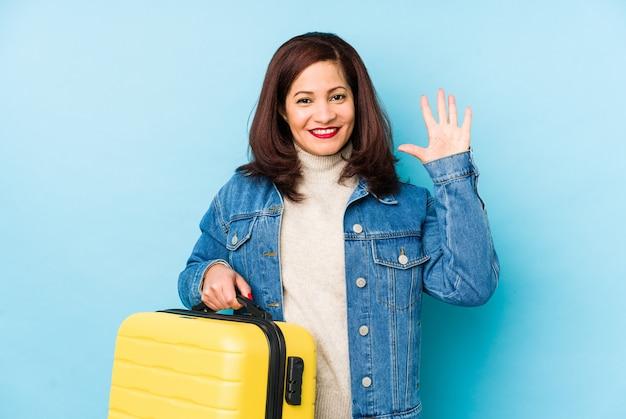スーツケースを持っているmiddlr年齢ラテン旅行者の女性