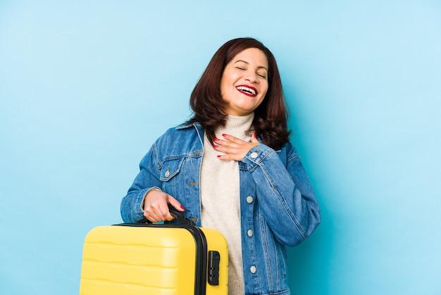 孤立したスーツケースを持っているmiddlrの年配のラテン旅行者の女性は胸に手を置いて大声で笑う