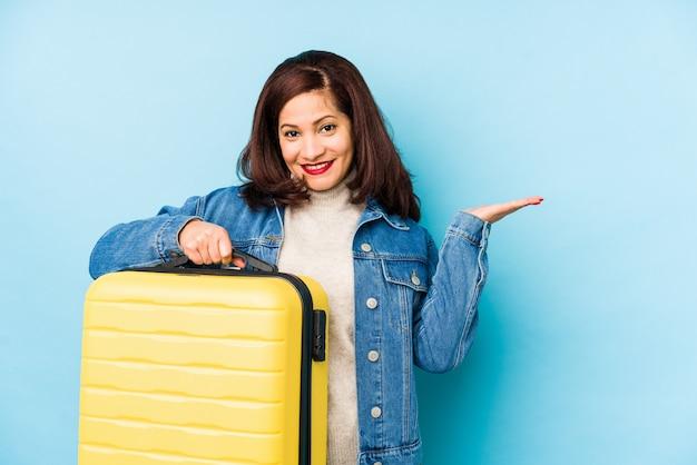 手のひらに何かを示し、トロリーバッグを保持しているスーツケースを保持しているmiddlr年齢旅行者女性