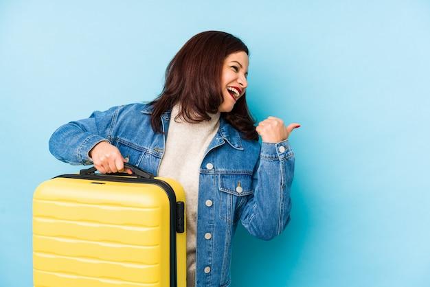 スーツケースを保持しているmiddlr年齢の旅行者女性が親指の指で離れて、笑って屈託のないポイントします。