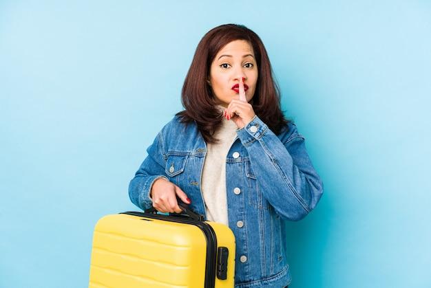 Middlr年齢ラテン旅行者の女性は、秘密を守るか沈黙を求めて分離されたスーツケースを保持しています。