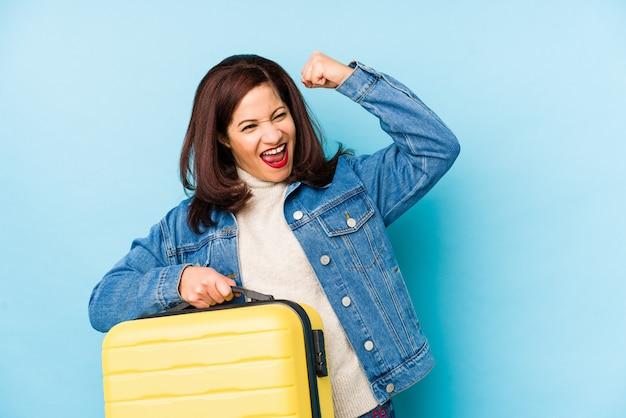 Женщина путешественника времени middlr латинская держа чемодан изолировала поднимать кулак после победы, концепцию победителя.