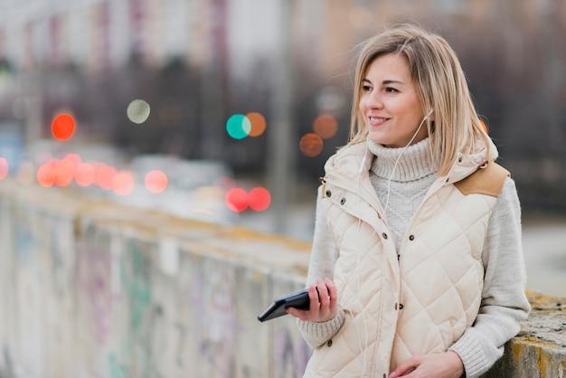 イヤホンと携帯電話を持つmidhsot女性