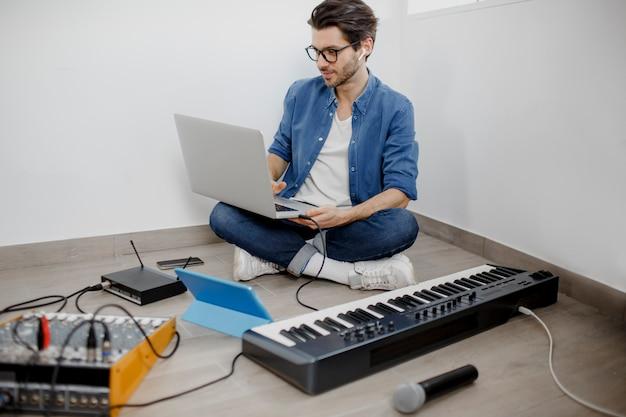 男は、自宅でプロジェクトの電子サウンドトラックまたはトラックを作成します。男性の音楽アレンジャーがデジタルスタジオでmidiピアノとオーディオ機器で曲を作曲しています。