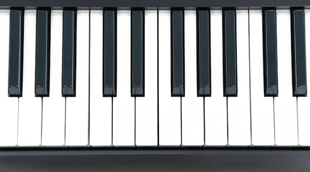 Ключ рояля крупного плана на деревянном столе с селективным фокусом, электронной клавиатурой синтезатора midi для творческой домашней студии