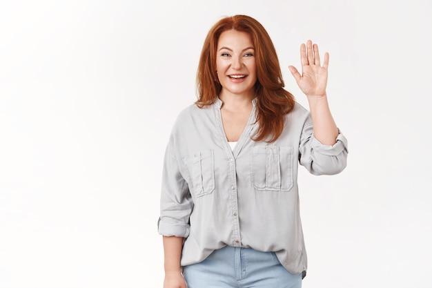 中年の赤毛の女性が会議に来て、こんにちはみんな知っているチームは手を振るフレンドリーなこんにちはジェスチャー笑顔の歯を見せる歓迎娘の友人が明るい白い壁に立っている