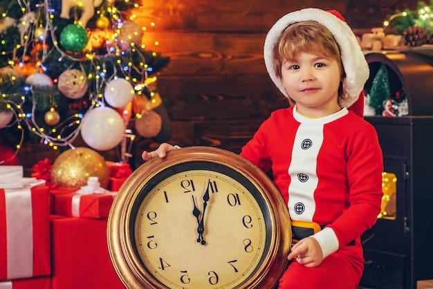 자정 기적. 새해 카운트 다운. 명랑하고 밝은 크리스마스. 아이는 크리스마스를 즐길 수 있습니다. 가족 휴가. 어린 시절의 추억. 산타 소년 어린 아이 크리스마스를 축하합니다. 크리스마스 트리 근처 소년 놀이입니다.