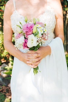 Midsection of a bride in white dress holding flower bouquet in her hands