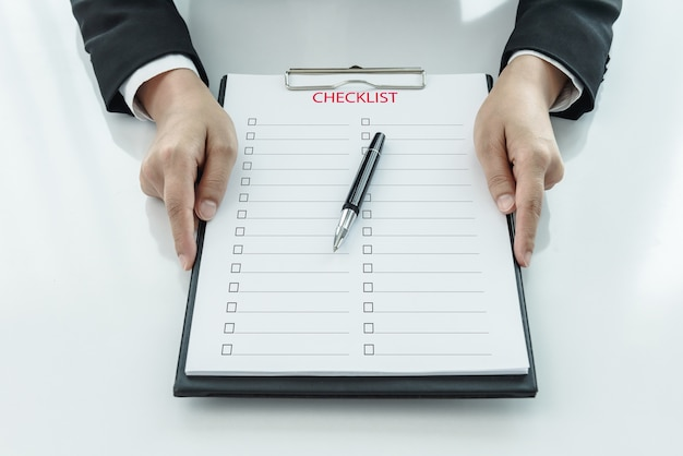 Midsection of businesswoman holding clipboard with checklist against