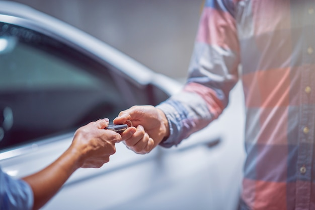 Midsection of car dealer giving keys to a customer